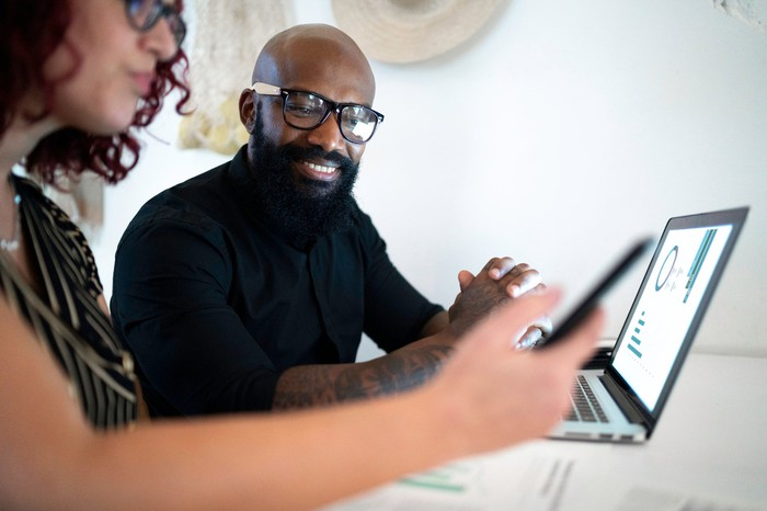 Two investors consider readouts on a laptop and a phone while sitting side by side as one smiles.