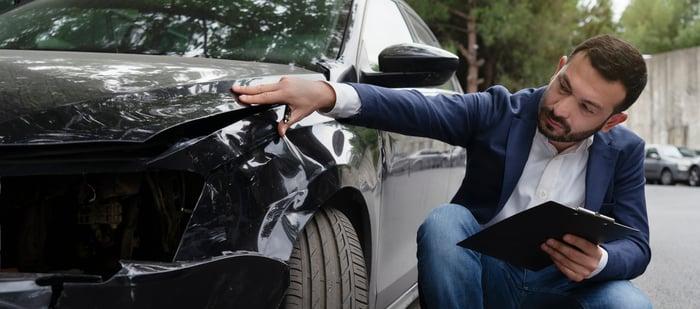 Man reviews car damage for an insurance claim.