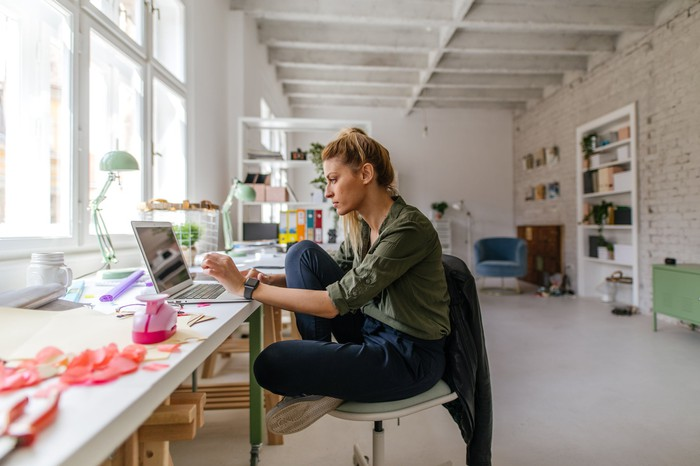 A younger worker sits at a laptop in a creative work space.