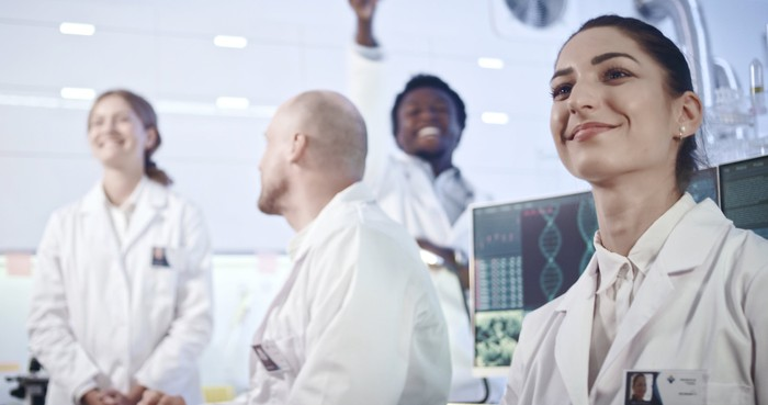 Four researchers smile in a laboratory setting.