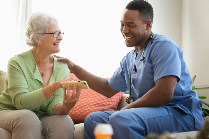A home healthcare worker sits with a patient.