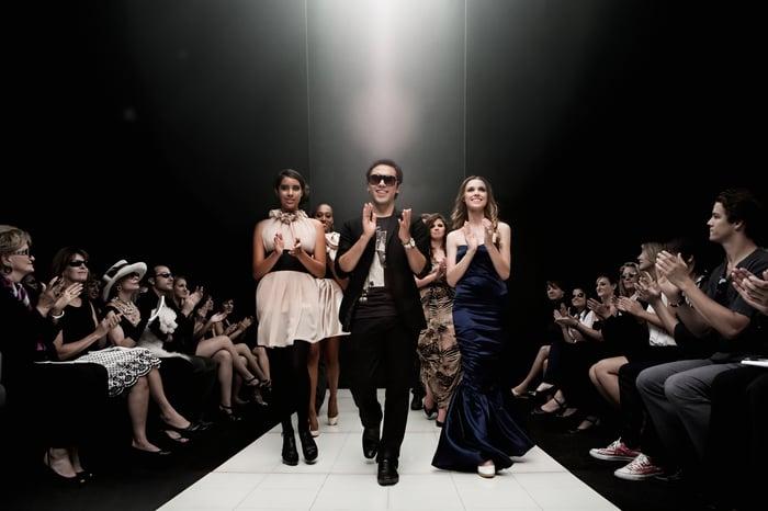 Les gens sur une piste de mode sous les projecteurs, avec des gens applaudissant de chaque côté.