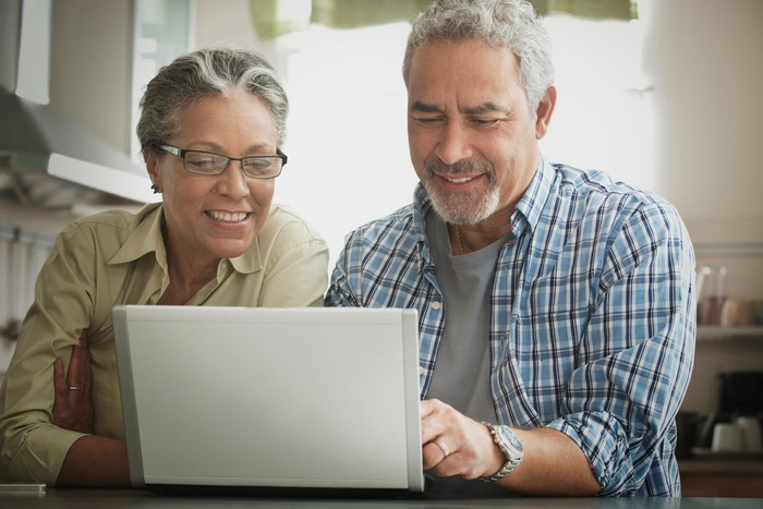 Two smiling people using a laptop.