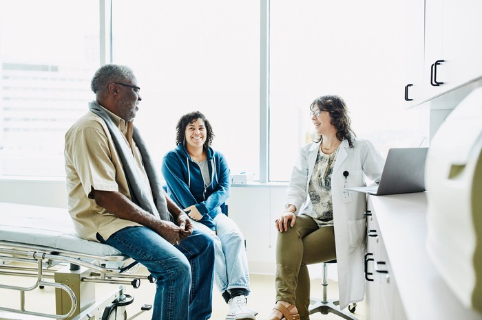 Medical professional consulting with a patient and their companion.