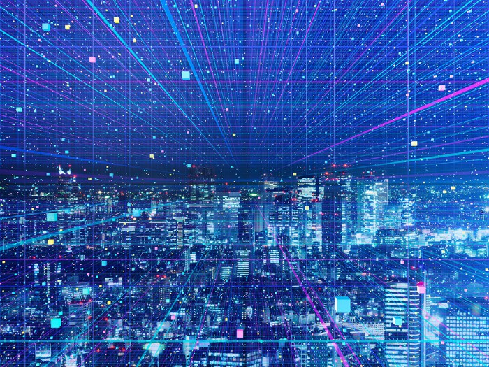 A cityscape at night, covered in digital color streaks.