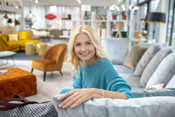 A smiling woman seated on a sectional couch in the middle of  a furniture expo.