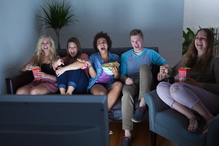 a group of five people sit on a couch and chair in a poorly lit room and laugh at a TV screen in the foreground