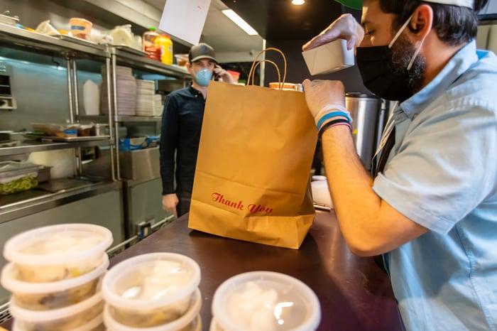 Restaurant worker preparing food for delivery driver.