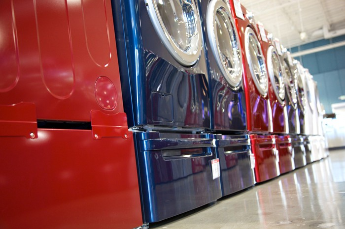 Colorful metallic red and blue washers and dryers lined up in a retail store.