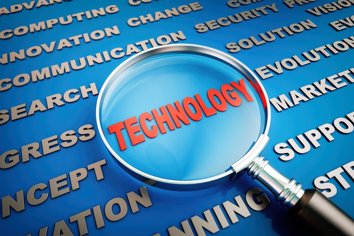 """Magnifying glass magnifying the word """"Technology"""" and surrounded by tech-related words."""