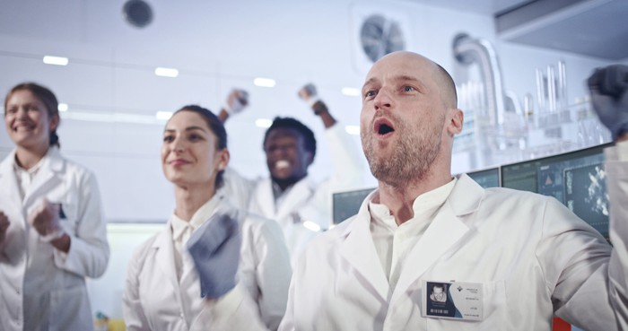 Scientists in white lab coats celebrating.