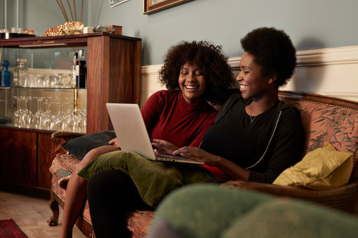 two people sit on a couch and smile while looking at a laptop.