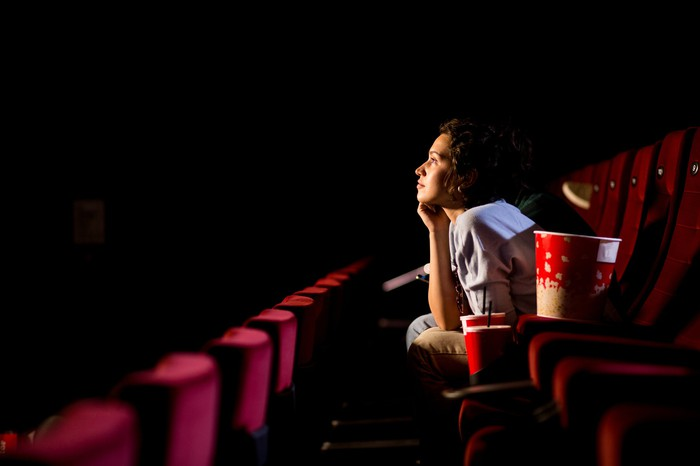Person sitting in an empty movie theater.