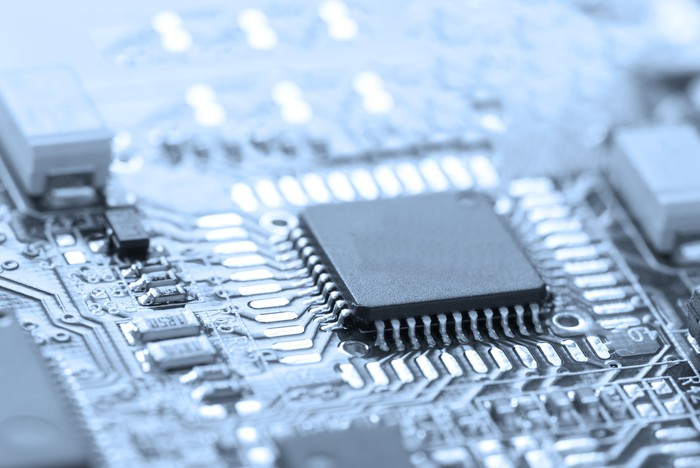 A black and white photo of a processor on a printed circuit board.