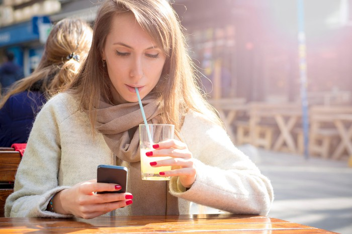 A smartphone user sips lemonade.