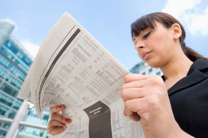 A woman reads a newspaper.