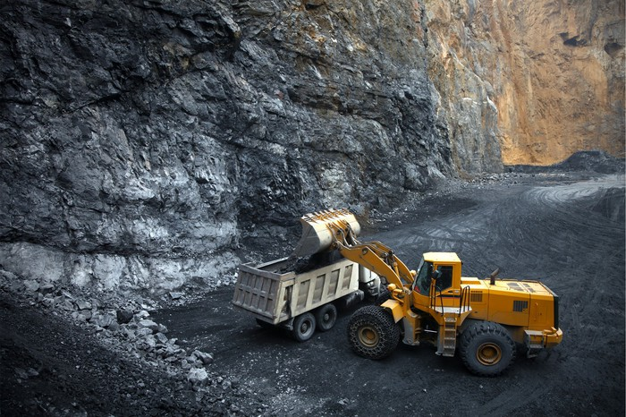Loader dumping minerals into a dump truck at a mining site.