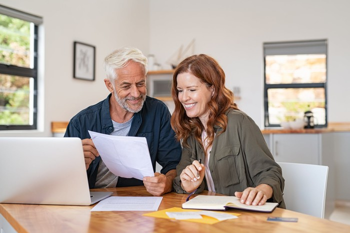 Smiling mature couple looking at a document.