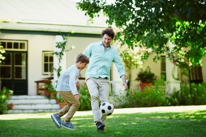 A person kicking a soccer ball with a child on the lawn in front of a house.
