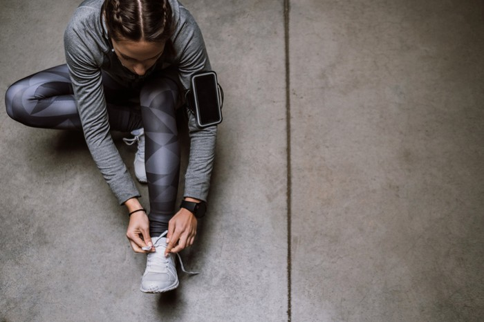 A person in workout clothes sitting on the floor and tying her shoelaces.