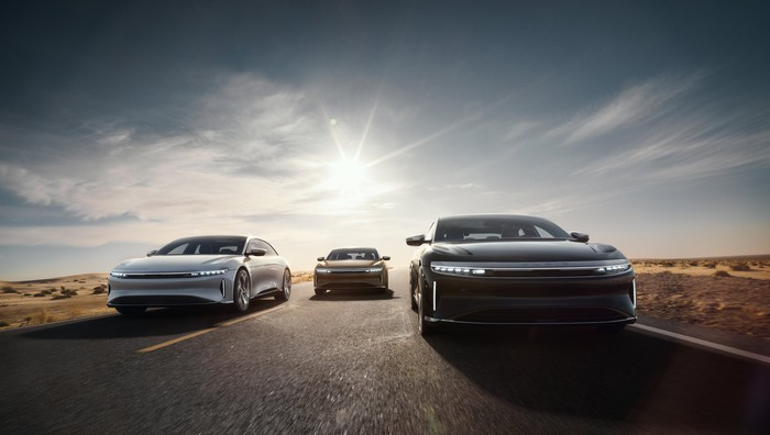 Three Lucid Air vehicles driving on a road.