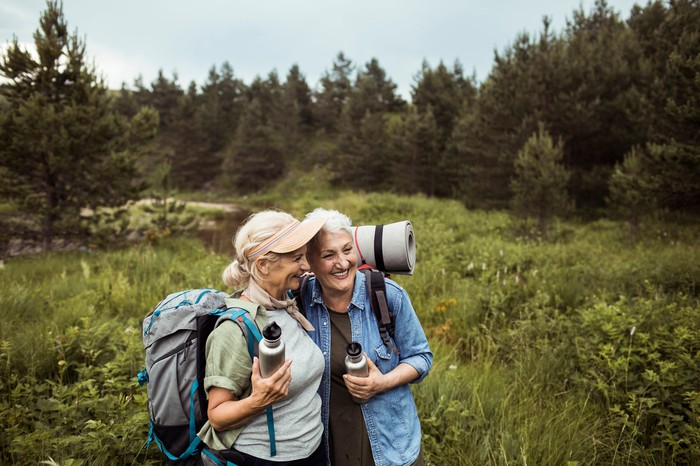 Two older adults hugging in a field while wearing hiking gear.