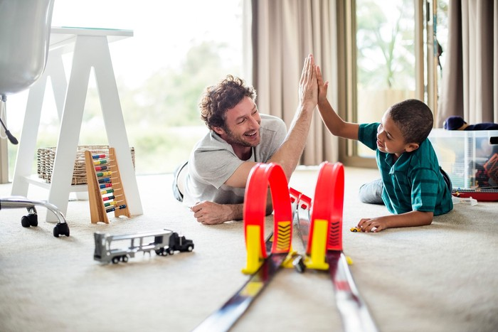 Adult and child playing with a toy race car track.