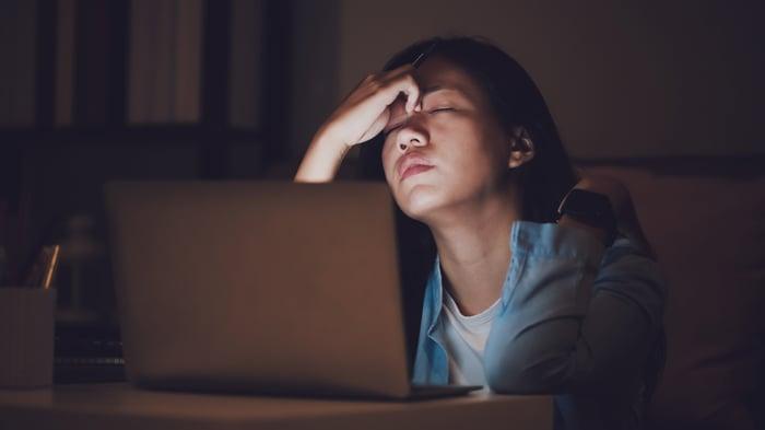Une personne se tient la tête et est assise les yeux fermés devant un écran d'ordinateur.