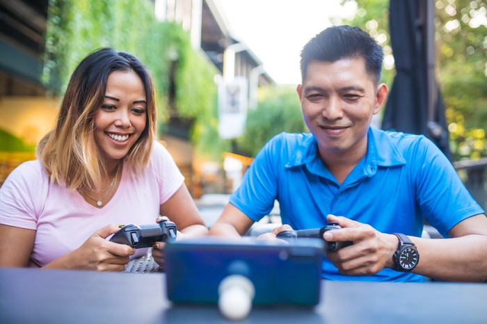 Two people play a mobile game using controllers, with the mobile phone propped up on a table.