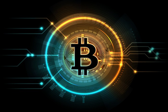 A colorful digital circle is surrounding a Bitcoin symbol on a black background.