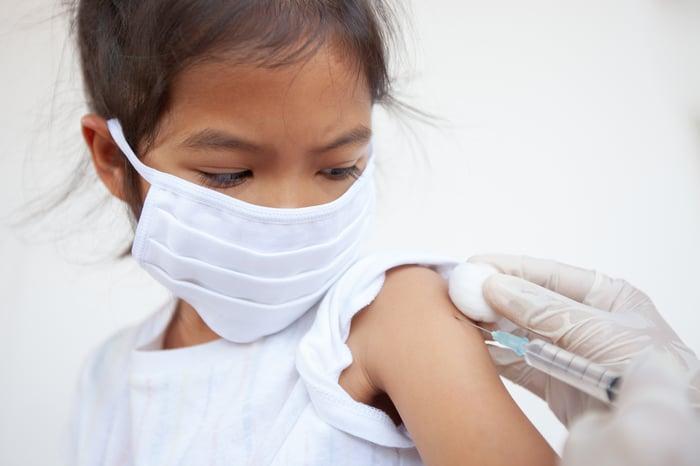 Enfant se faisant vacciner par un professionnel de la santé.