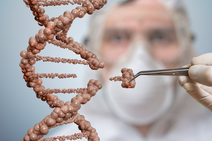 A person in a mask editing a double-helilx DNA strand.