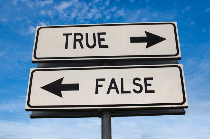 """Road signs pointing in opposite directions to """"true"""" and """"false."""""""