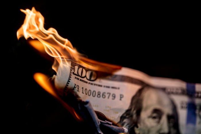 A one-hundred dollar bill is on fire.