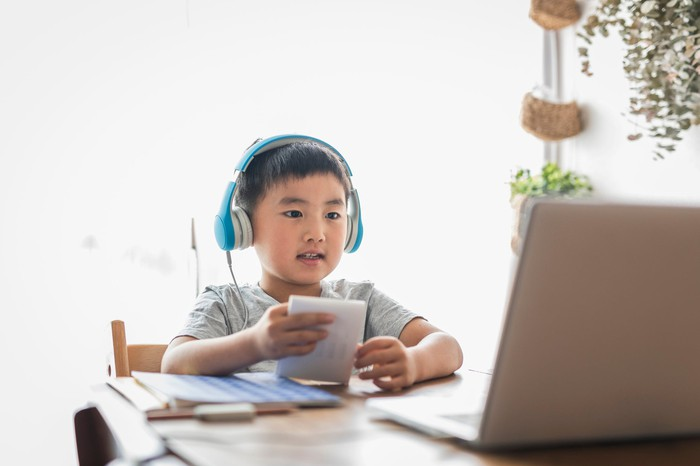 A child wearing headphones is looking at a laptop screen.
