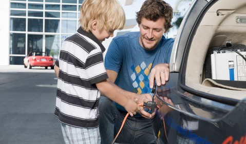 Father and son attaching electrical plug to electric car.