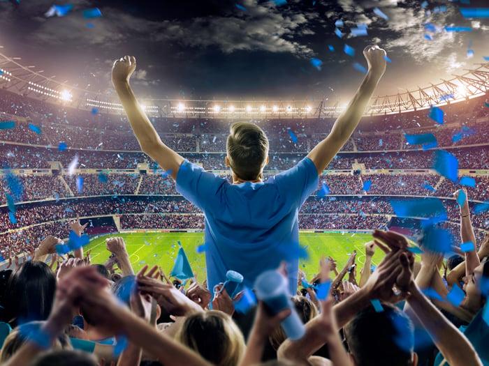 Fan cheering in stadium among a huge crowd.