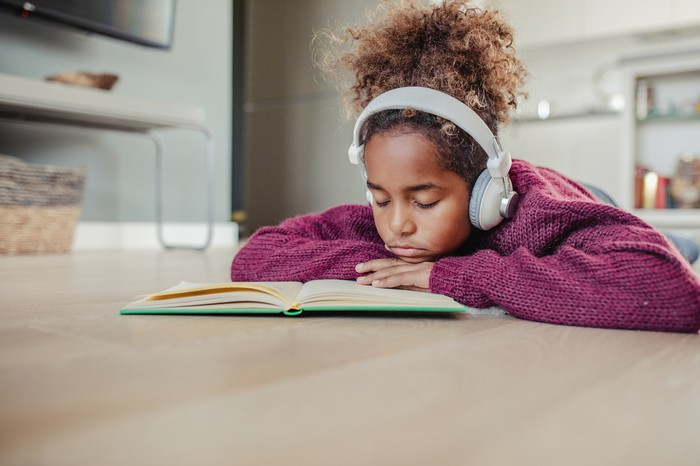 Young person frowning over a book, wearing headphones.