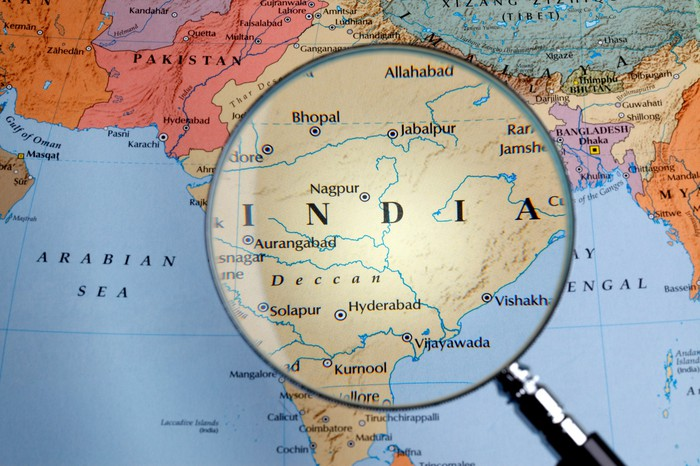 Magnifying glass over India on portion of world map.