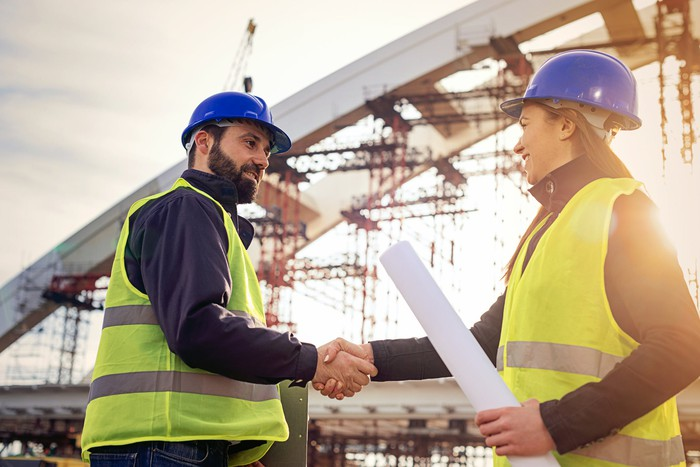 People shaking hands at a construction site.