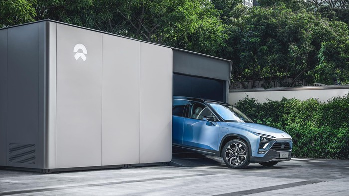A NIO ES8, an upscale electric SUV, is shown driving out of one of the company's automated battery-swap stations.