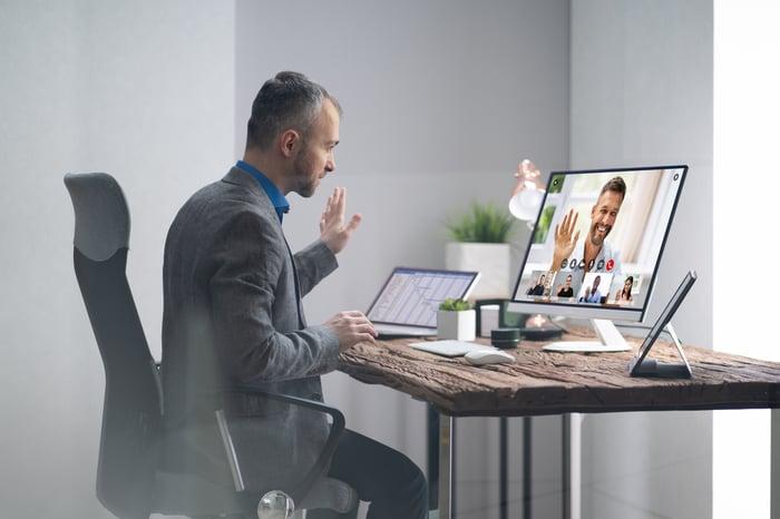 A businessperson using a webcam during a virtual meeting.
