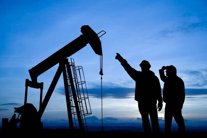 Silhouette of two people pointing to an oil well.