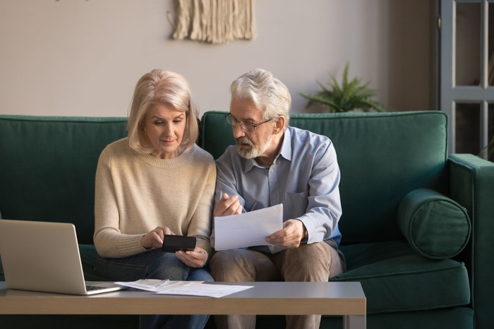 Two older people sitting on a couch looking at documents.
