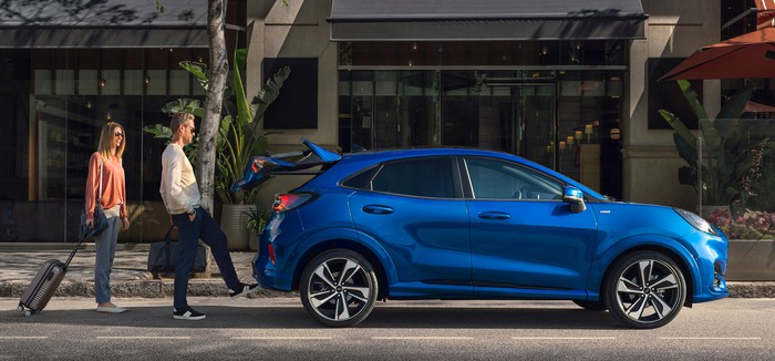 A blue Ford Puma, a small sporty SUV, parked at a curb.