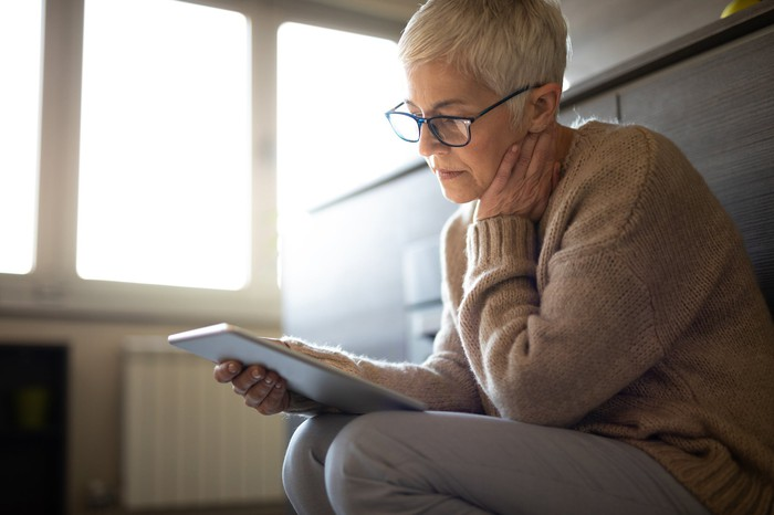 Mature woman staring at a tablet with a worried look on her face.