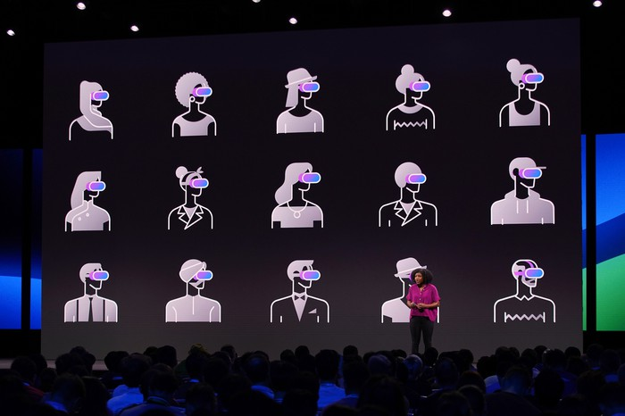 A woman presents on stage, with graphics behind her on screen. The graphics are of cartoon humans wearing VR headsets.