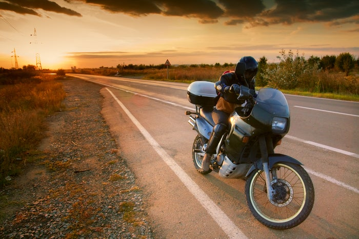 A motorcyclist on the road with the sun rising or setting in the background.