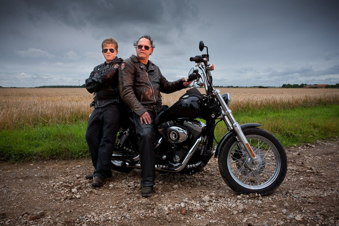 Parent and offspring with a large Harley-type motorcycle, representing continuation of the motorcycling trend across generations.