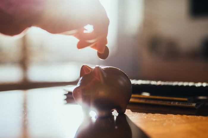 Tirelire assise sur une table avec une main planant au-dessus tenant une pièce de monnaie.